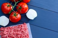 Семенить мясо с красными томатами на ветви и отрезанных луках на серой деревянной предпосылке с космосом экземпляра Стоковое Фото