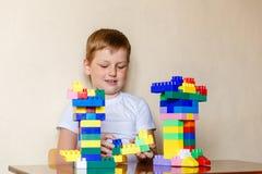 Семилетний ребенок играя с большими частями дизайнера стоковое изображение rf