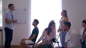 Семинар дела, молодые успешные люди поднимает руки для того чтобы сказать мысли о развитии идей дела на active сток-видео