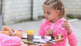Семилетняя девушка выбирает правый чертеж в альбоме, усаживание чернил цвета на таблице с другой девушкой видеоматериал