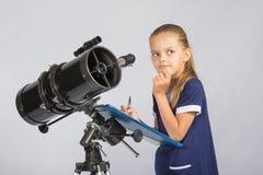 Семилетняя девушка заботливая смотрящ небо, делая запись замечаний в телескопе Стоковая Фотография