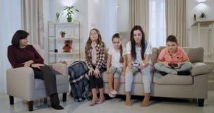 Семьи выходных мать совместно с ее 3 детьми играя на видеоигре перед камерой используя PSP очень видеоматериал