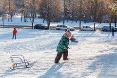Семьи наслаждаются sledding на снежном холме Стоковое Изображение