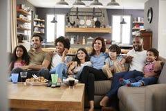 2 семьи сидя на софе смотря телевидение совместно стоковые фото