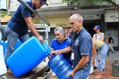 Семьи собранные вверх по пластиковым бутылкам для того чтобы заполнить их со шлангами мочат в Каракасе, Венесуэле стоковые фотографии rf