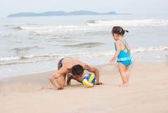 Семья Азиатский ребёнок и отец играя футбол на пляже Стоковое фото RF