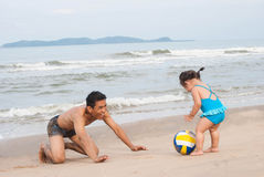 Семья Азиатский ребёнок и отец играя футбол на пляже Стоковое Изображение