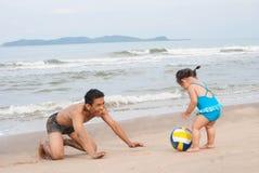 Семья Азиатский ребёнок и отец играя футбол на пляже Стоковые Фото