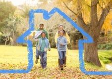 Семья бежать в парке против плана дома в предпосылке Стоковые Изображения RF