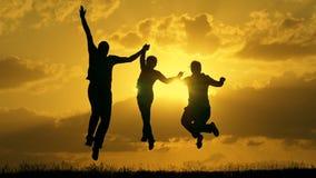 Семья бежать на заходе солнца и скача вверх по поднимать их победителей рук сток-видео