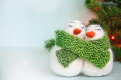 Семья белых счастливых любящих пушистых снеговиков шерстей с зеленым цветом связала шарф около рождественской елки с светами на я стоковое фото rf