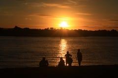 Семья во время захода солнца Стоковая Фотография RF