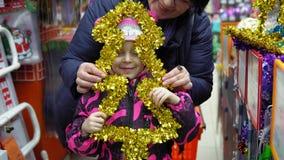 Семья выбирает искусственную рождественскую елку, украшения Xmas в магазине сток-видео