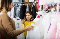 Семья выбирая платье в магазине Стоковые Фото