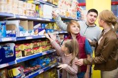 Семья выбирая хлопья в супермаркете стоковое фото