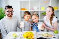 Семья выпивает молоко для завтрака стоковые фотографии rf