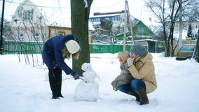 Семья в зиме в парке ваяет снеговик сток-видео