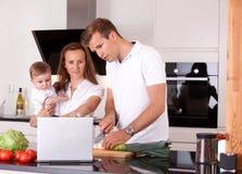 Семья в кухне подготовляя еду Стоковая Фотография