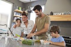 Семья в кухне после рецепта на таблетке цифров совместно стоковое изображение rf