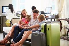 Семья в лобби гостиницы смотря таблетку цифров Стоковая Фотография