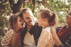 Семья в парке имея переговор и обнимать стоковое изображение rf