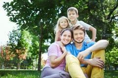 Семья в полдень в парке на траве Стоковое фото RF