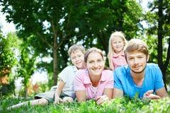 Семья в полдень в парке на траве Стоковая Фотография