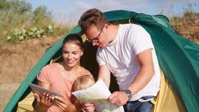 Семья в шатре лагеря проверяя положение с пусковой площадкой и картой видеоматериал