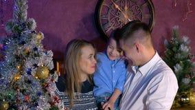Семья говорит и смеется над около рождественской елки на торжестве Нового Года акции видеоматериалы