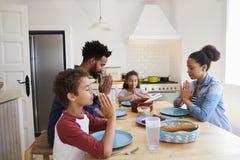 Семья говоря грациозность на кухонном столе перед их едой Стоковое Фото