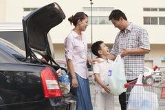 Семья говоря рядом с автомобилем с хозяйственными сумками Стоковое Изображение