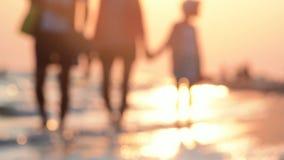 Семья гуляет вдоль seashore на заходе солнца Счастливая семья на каникулах акции видеоматериалы