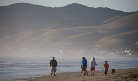 Семья гуляя на пляж стоковое изображение rf