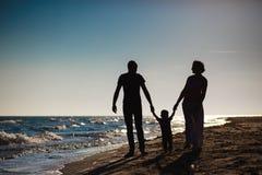 Семья гуляя на пляж на заходе солнца Стоковая Фотография RF