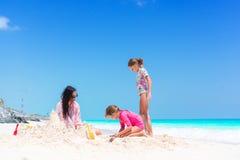 Семья делая замок песка на тропическом белом пляже Будьте матерью и 2 девушки играя с песком на тропическом пляже Стоковые Фото