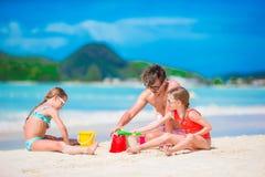 Семья делая замок песка на тропическом белом пляже Будьте отцом и 2 девушки играя с песком на тропическом пляже Стоковое фото RF
