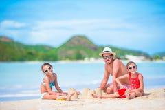 Семья делая замок песка на тропическом белом пляже Будьте отцом и 2 девушки играя с песком на тропическом пляже Стоковое Изображение RF