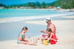 Семья делая замок песка на тропическом белом пляже Стоковое Изображение