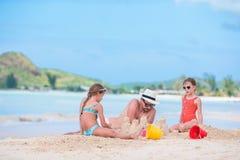 Семья делая замок песка на тропическом белом пляже Стоковые Фотографии RF