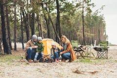 семья делая лагерный костер совместно пока имеющ отключение стоковая фотография rf