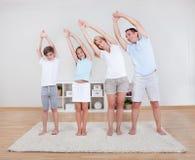 Семья делая протягивающ тренировки на ковре Стоковое Изображение