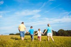 Семья держа руки бежать над лугом Стоковое Изображение