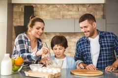 Семья дома стоя около таблицы в отце кухни совместно и матери сына наблюдая юркнуть ингредиенты радостные стоковое фото rf