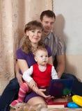 Семья дома с компьтер-книжкой Стоковые Фотографии RF
