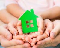 Семья держа дом зеленой книги Стоковая Фотография
