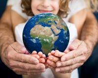 Семья держа планету земли в руках Стоковые Изображения