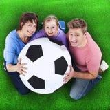 Семья держит футбольный мяч стоковые изображения rf