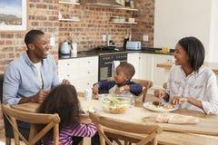 Семья есть еду в открытой кухне плана совместно стоковые фото