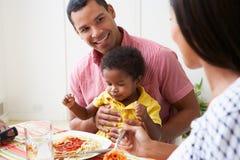 Семья есть еду совместно дома Стоковые Изображения