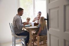 Семья есть на таблице в sunlit комнате Стоковые Фотографии RF